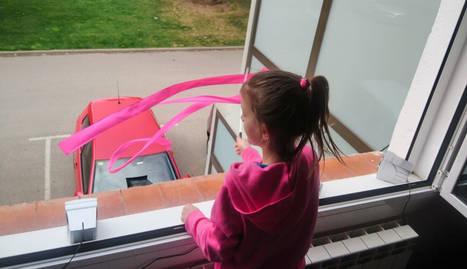 Una nena mentre balla a la finestra de casa seva.