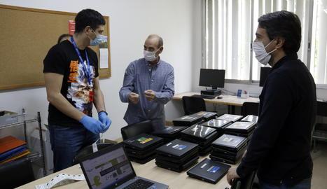 Responsables de l'institut Josep Lladonosa i tècnics preparen els ordinadors.