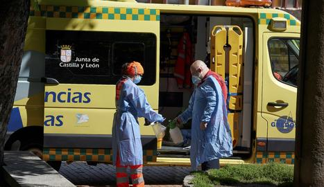 Un equip d'emergències desinfecta els seus elements de protecció després d'atendre una urgència en un carrer d'Àvila
