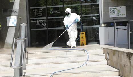Un operari desinfecta l'entrada de l'hospital Santa Maria.
