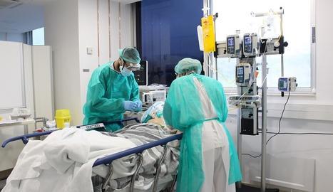 Dos metges atenen un pacient amb coronavirus.