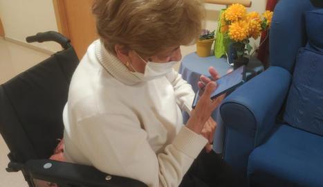 Una usuària de la residència de Guissona parla amb un familiar amb un dels mòbils que ha entregat Salut.
