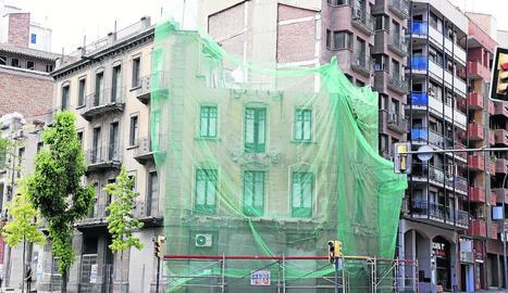 Imatge de la façana, que està tapada, sense els pisos superiors.