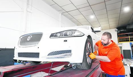 Un treballador d'un taller desinfecta un vehicle, una mesura que han de prendre tant quan entra com abans de sortir del taller.