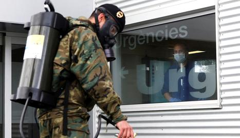 Un pacient observa l'actuació de membres de l'Exèrcit que treballen desinfectant els voltants de l'Hospital Trias i Pujol (Can Ruti ) de Badalona.