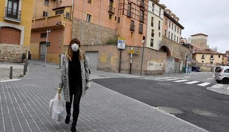Una dona caminant ahir pel centre de Lleó amb mascareta i una bossa de comprar.