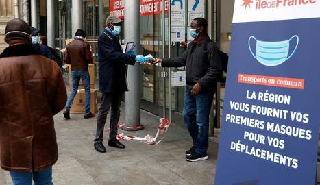 Un voluntari reparteix mascaretes en una estació de París.