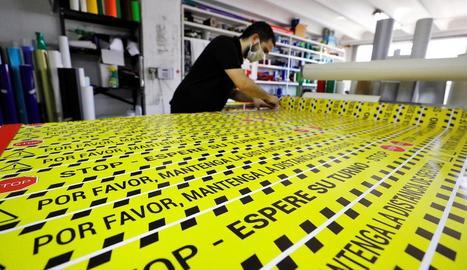 Elaboració de rètols per marcar distàncies entre clients dels negocis que reobriran ben aviat.