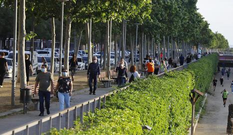 Passejants pel carrer Jaume II mentre els esportistes corren per la canalització