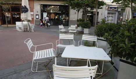 Part de la terrassa d'un local de restauració de Lleida, amb cadires i taules desplegades al carrer.