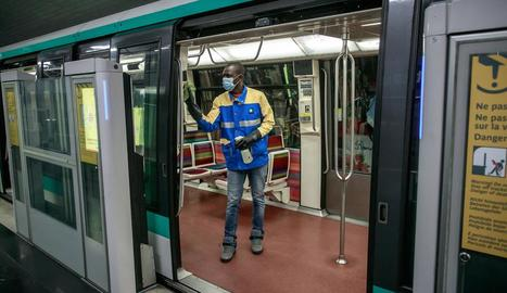 Un operari porta a terme tasques de desinfecció en un vagó de metro a França.