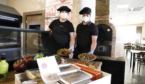 Dos cuiners de Casa Tere ensenyen els plats abans del repartiment.