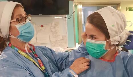 Una sanitària n'ajuda una altra a col·locar-se la mascareta en un centre de Lleida.