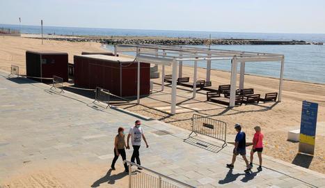 Algunes persones passejant ahir pel passeig marítim de la platja del Bogatell a Barcelona.