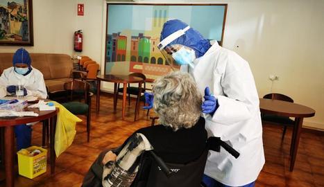 Sanitaris extreuen la mostra per a la PCR a una usuària de la residència Sant Domènec de Balaguer.