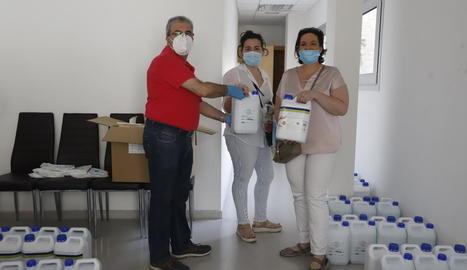 A l'esquerra, el president de l'Eix, Llorenç González, entrega el kit sanitari a una comercianta. A la dreta, una dona surt d'una botiga que ofereix serveis de cita prèvia.