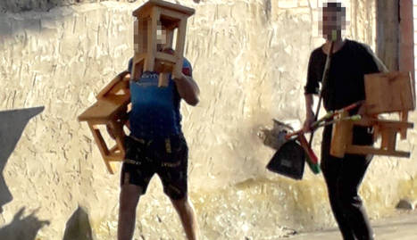 Dos joves amb tamborets del bar Rasep, tancat, a la Granja d'Escarp.