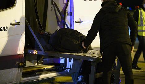 Un dels espanyols repatriats de la ciutat xinesa de Wuhan pel risc de coronavirus carrega maletes en un autobús abans de ser traslladat a l'hospital per la quarantena el 31 de gener.
