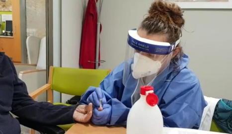 Una sanitària fent una prova en una residència.