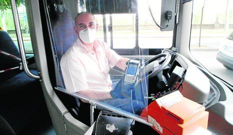 Un conductor d'autobús mostra el datàfon rere la mampara.