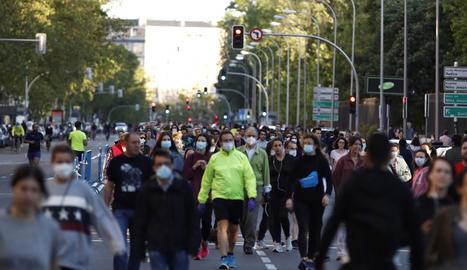 Nombroses persones passejant diumenge per una carretera convertida en zona de vianants a Madrid.
