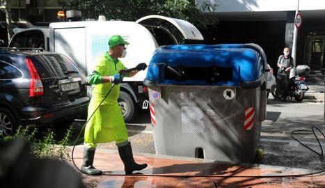 Un operari neteja un contenidor, ahir, al costat dels Jardins de Montserrat, a Barcelona.