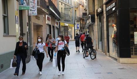 Tres dones passejant ahir a la tarda per l'Eix Comercial de Lleida carregades amb bosses.