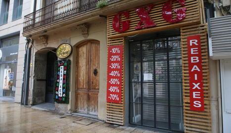 Botigues tancades a l'Eix Comercial amb anuncis de rebaixes.
