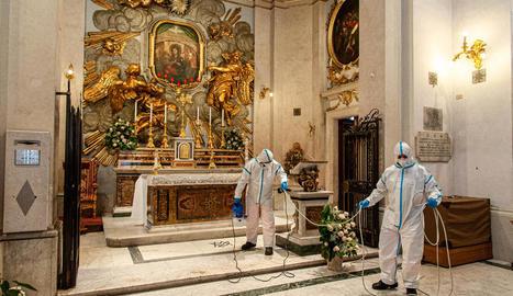 Equips de neteja desinfecten un altar en una església a Roma.