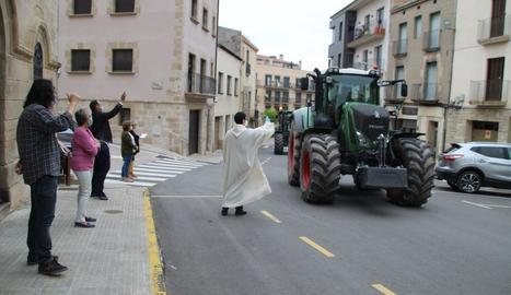 El mossèn de Bellpuig beneint un dels tractors participants en la desfilada dels Tres Tombs.