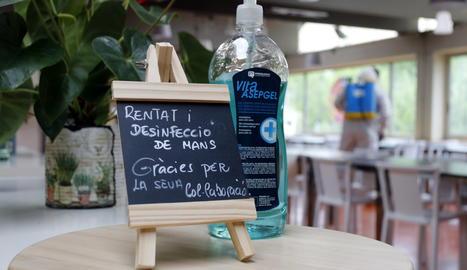 Un cartell i una ampolla de gel desinfectant, mentre al fons un treballador del restaurant El Gat de Tàrrega desinfecta el local.