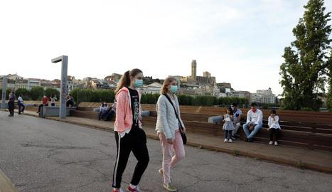 Dos dones passegen per la passarel·la del Liceu Escolar amb mascareta.