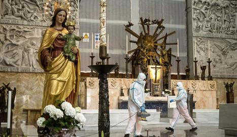 Operaris desinfecten l'església de Sant Joan Bosco de Roma, que podrà reobrir demà.