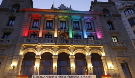 Bandera multicolor al balcó de l'ajuntament de les Borges i façana de la Paeria de Lleida il·luminada amb els colors de l'arc de Sant Martí.