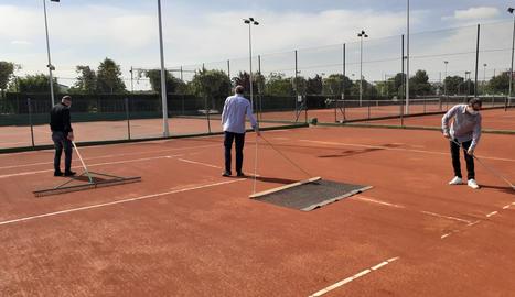 Un operari desinfecta l'entrada al recinte del Club Tennis Urgell, que també va posar a punt les pistes per a la reobertura avui de les instal·lacions