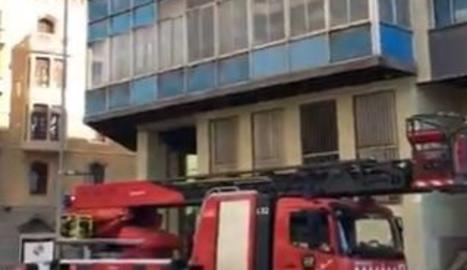 El bombers sanegen la façana de l'edifici dels sindicats de Lleida, amb un panell de vidre a punt de caure