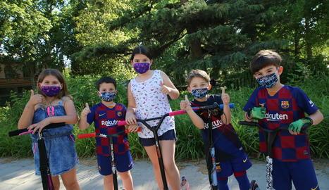 Nens jugant ahir amb patinet pels carrers de Lleida, amb mascaretes infantils