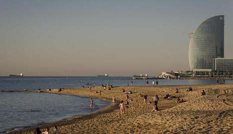 Desenes de persones a primera hora en una platja de Barcelona. Alguns prenen el sol tot i les normes.