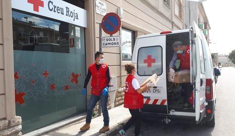 Repartiment de material escolar i didàctic de voluntaris de Creu Roja a Cervera.
