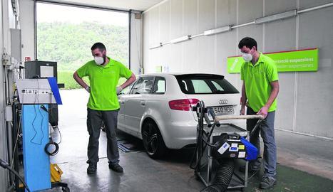 Dos operaris de l'empresa Certio revisen un vehicle a l'estació d'ITV de Montferrer.