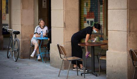 Una cambrera desinfecta les taules i les cadires en un bar de Barcelona.