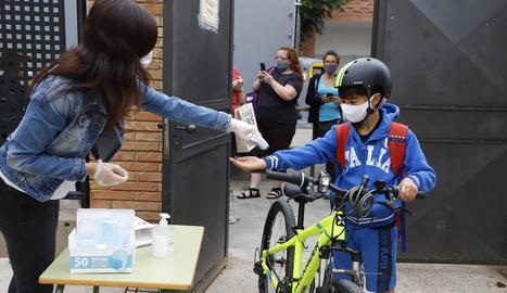 Una professora pren la temperatura a una alumna a l'escola Arrels de Solsona.
