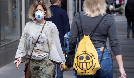 Una dona passeja protegida amb una mascareta a Múrcia.