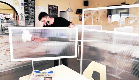 L'amo d'un bar restaurant de Lleida prepara l'interior del local amb mampares entre les taules.
