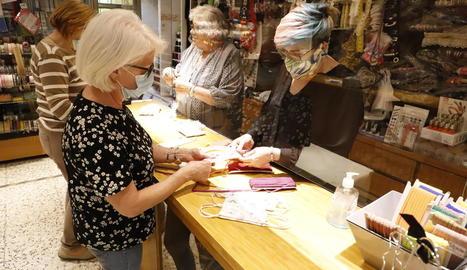 Imatge d'una merceria, on les empleades atenen els clients a través d'una mampara.