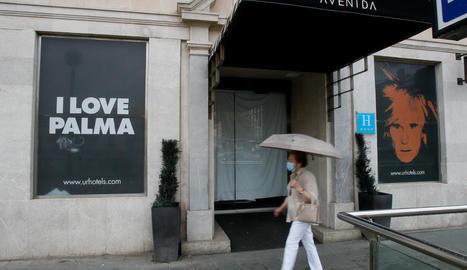 Una dona passa per davant d'un hotel encara tancat a Palma de Mallorca.