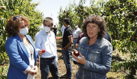 La consellera Jordà mostra una nectarina destrossada en un camp de Soses al costat de l'alcaldessa.