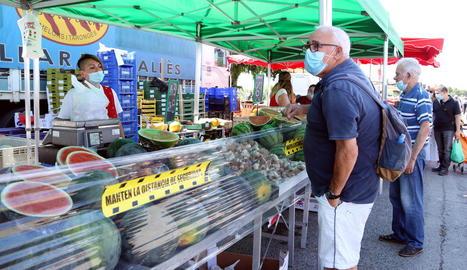 Clients amb mascaretes en una parada de fruita al mercadillo de Bonavista de Reus.
