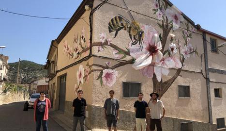 L'alcaldessa d'Os de Balaguer, el gerent de Torrons i Mel Alemany i els tres artistes, davant del mural.