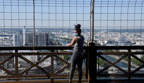 Una visitant de la Torre Eiffel, ahir, amb la ciutat de París de fons.